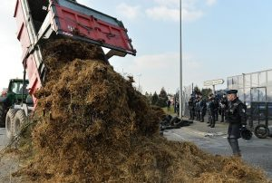 French farmers dump straw as they block the access to the Lactalis factory on March 23, 2016, in Laval, northwestern France during a demonstration to protest against falling prices of dairy products. / AFP / JEAN-FRANCOIS MONIER (Photo credit should read JEAN-FRANCOIS MONIER/AFP/Getty Images)